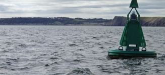 The buoy astern marks the channel between Tenby and Caldy Island.  In the distance is the Holiday Village of Lystep.