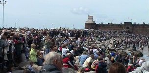 Crowds throng at New Brighton Marine Lake and smother Fort Perch Rock to watch tall ships