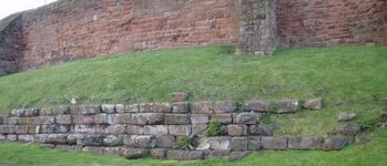 Original harbour wall beneath the buttressed mediaeval city wall.