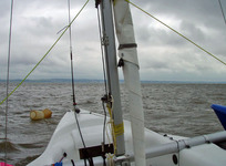 Note the temporary, yellow, diagonal shrouds stabilising the mast and the main sheet attached to the bow for mast raising.
