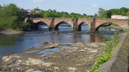 The Old Dee Bridge at low water with Roman ford in foreground.