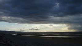 Looking back from Towyn towards the Great Orme's Head with Snowdonia rising to the left of the picture.